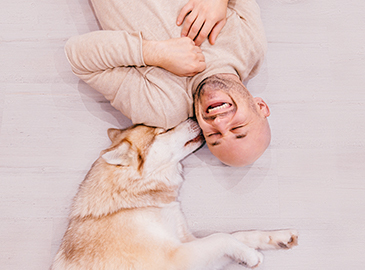 man laying on the floor with a dog licking his cheek