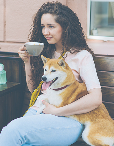 woman drinking tea and hugging dog outdoors in cafe sitting