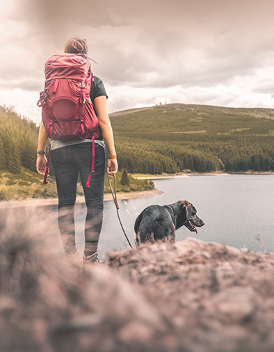 woman with backpack and german shepherd dog puppy standing on mountain in front of forest and lake